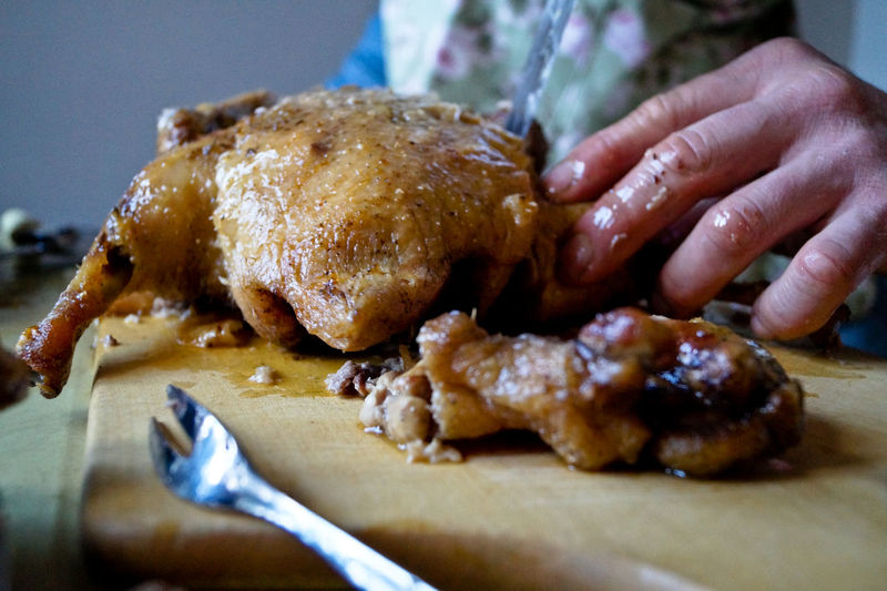 Cropped Image Of Hand Cutting Roasted Duck On Board