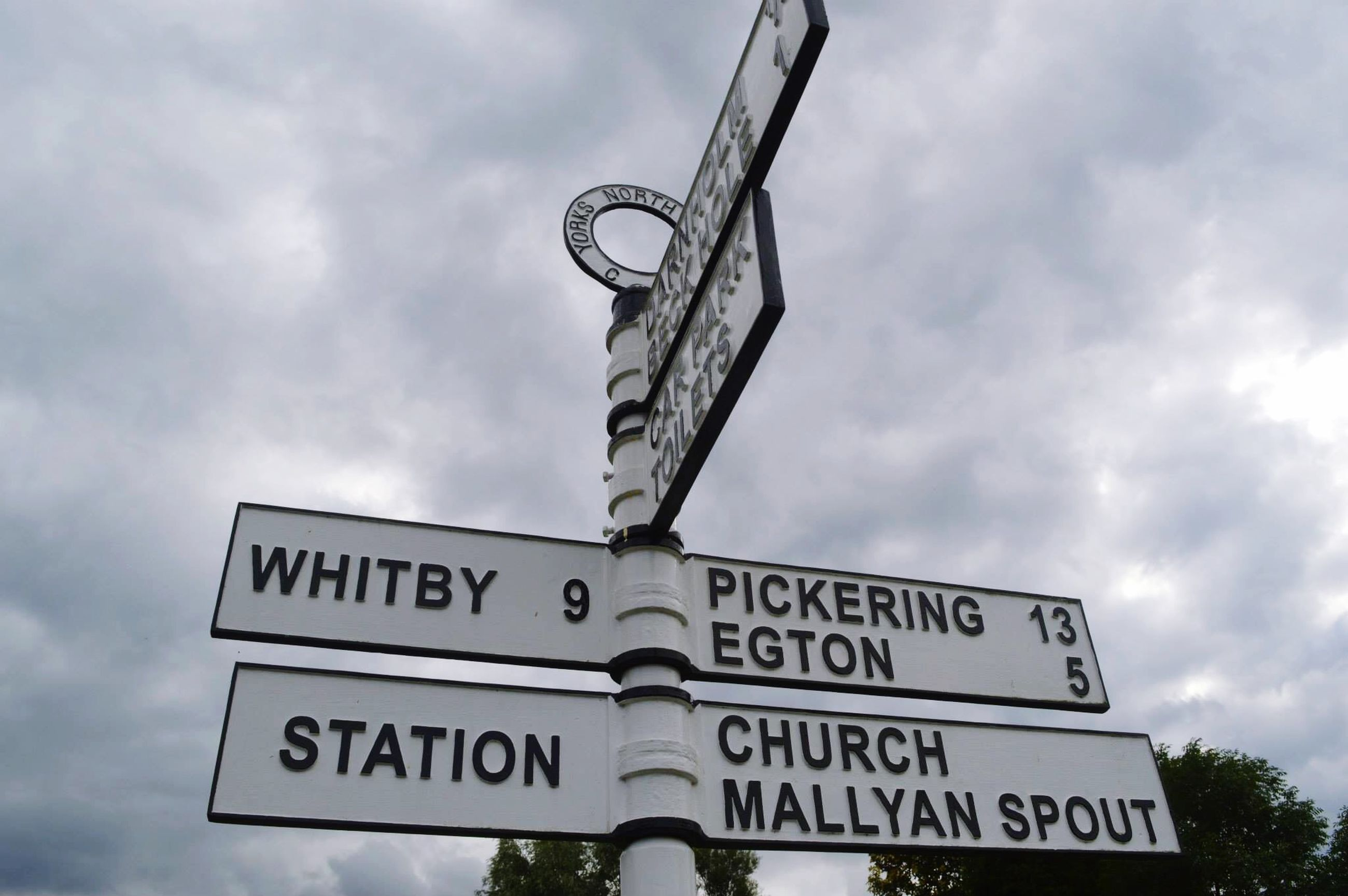 text, communication, western script, low angle view, sky, information sign, cloud - sky, sign, information, cloudy, guidance, capital letter, non-western script, road sign, directional sign, cloud, warning sign, direction, arrow symbol, human representation