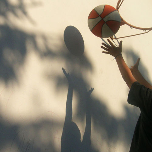 Low angle view of person playing with ball against sky