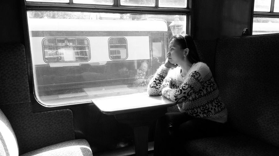 Thoughtful Woman Sitting By Window In Train