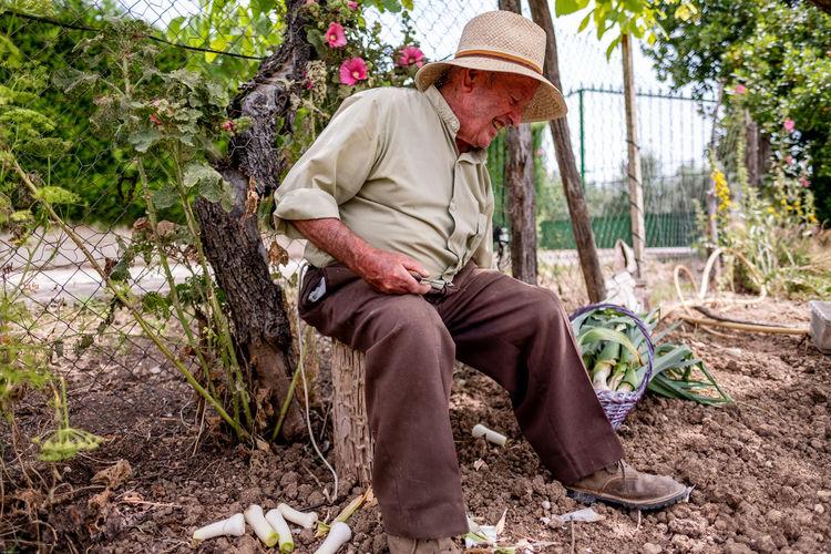 Full length of senior man sitting by plants