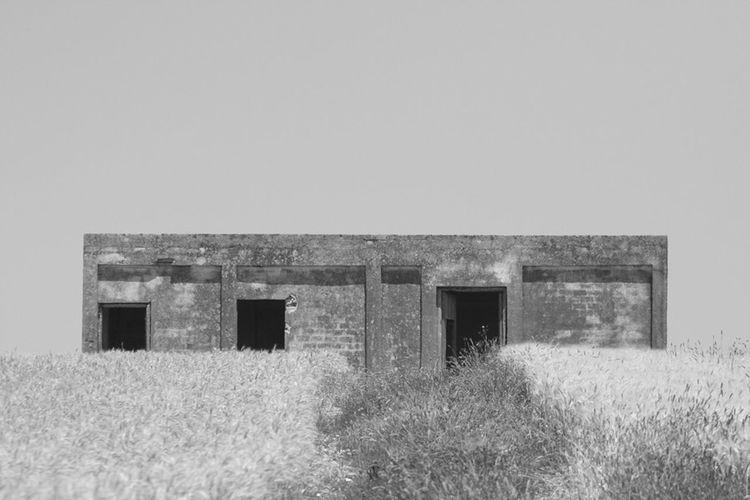 Old barn on field against clear sky