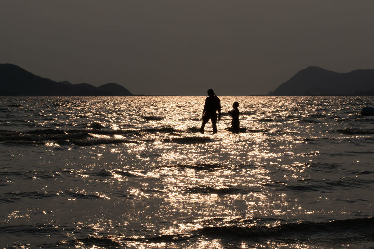 Silhouette people on sea by mountains against clear sky
