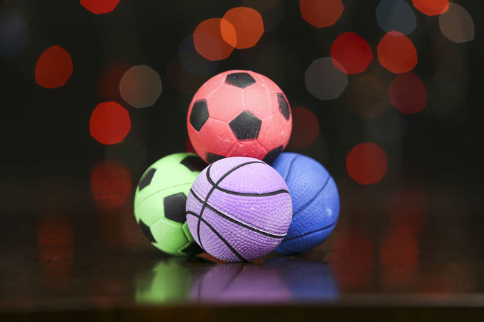 Rubber ball in wooden table with light blur background Colors Art And Craft Ball Close-up Colorful Design Focus On Foreground Illuminated Indoors  Lens Flare Multi Colored Night No People Pattern Rubber Ball Rubber Balls Shape Soccer Soccer Ball Sphere Sport Sports Equipment Still Life Team Sport Toy