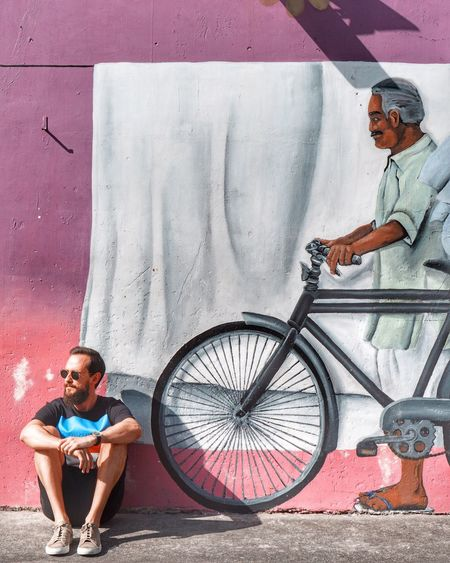 Bicycle Wall - Building Feature Casual Clothing Lifestyles Real People People Young Adult Transportation Young Men Graffiti Day Front View Glasses Sunglasses Full Length Leisure Activity Shorts Men Standing Outdoors