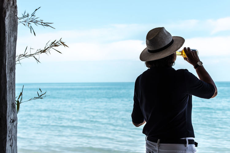 Beach Beauty In Nature Beer Black Sea Cloud - Sky Day Hat Horizon Over Water Leisure Activity Lifestyles Live For The Story One Person Outdoors The Street Photographer - 2017 EyeEm Awards Photography Themes Real People Rear View Scenics Sea Sky Standing Sommergefühle Water Woman Woman With Hat