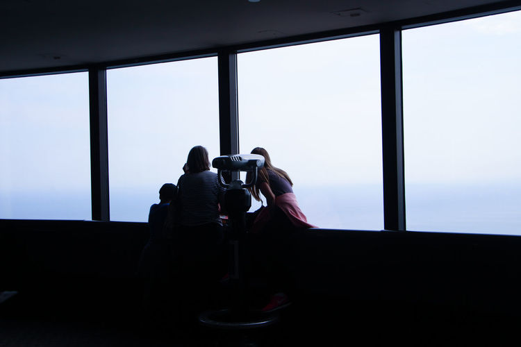 Tourists looking sky through observation point