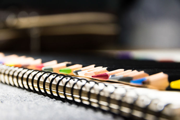 Close-up of multi colored pencils with note pad on table