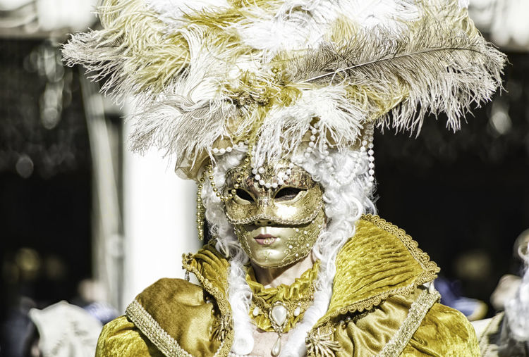 Portrait of a beautiful woman in a yellow dress and golden mask with feathers and pearls during the Venetian carnival party in San Marco square Carnival Disguise Feathers Gold Lady Masque Tradition Venetian Woman Carneval Close-up Costume Disguise Dressing Festival Hide Italy Mask Masquerade Mistery Pearls San Marco Traditional Unrecognizable Venice