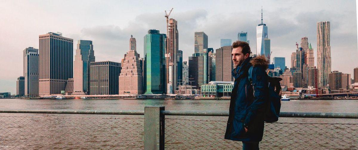 Man standing by modern buildings in city against sky