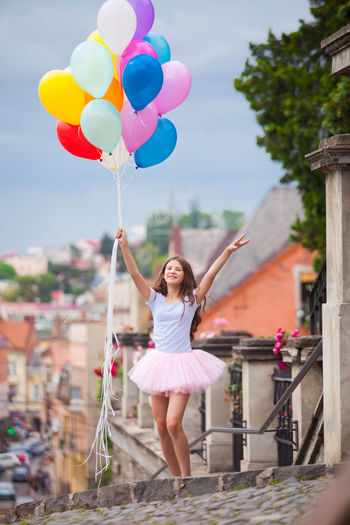 Full length of woman holding colorful balloons