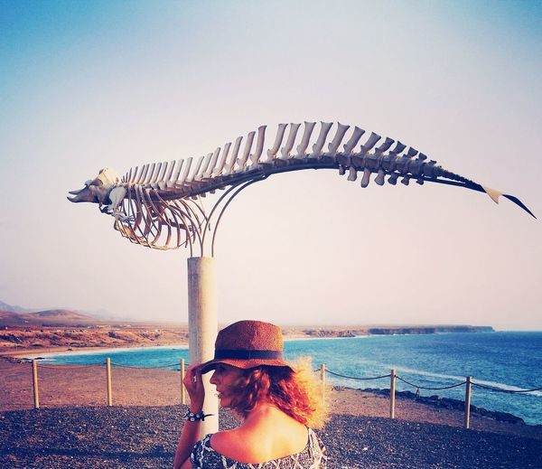 Woman standing by animal skeleton at beach against sky