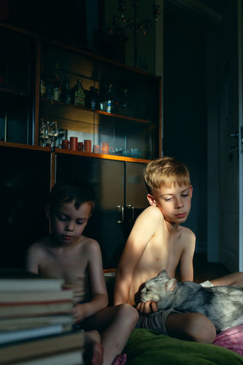 Portrait of shirtless boy sitting at home