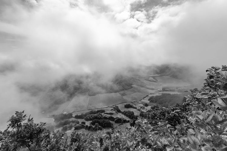 Black and white view of Pastures in the Sete Cidades caldera from the rim in Sao Miguel. Sete Cidades Azores Azorean Açores Sao Miguel Crater Caldera Caldeira Alferes Village Lagoa Azul Verde Clouds Farm Pasture Hike View Landscape Tourism Trek Volcano Black And White