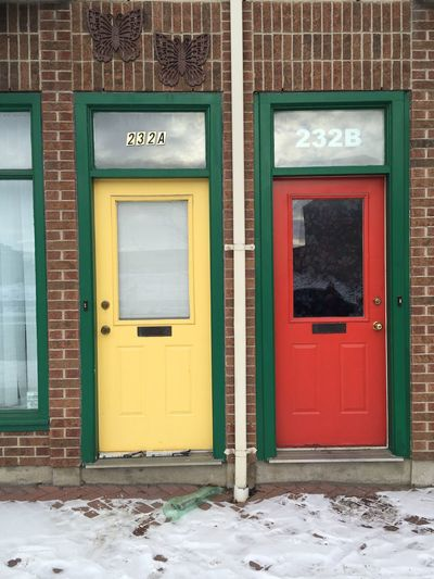 Closed Red And Yellow Doors On Brick Wall