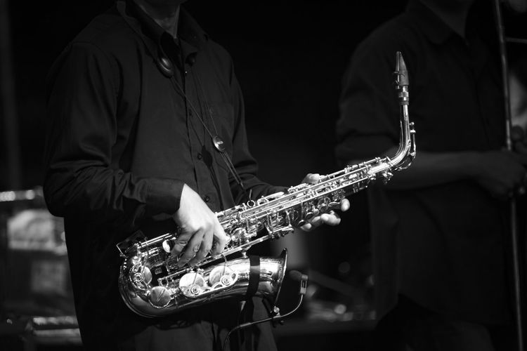 Midsection Of Man Playing Saxophone In Darkroom