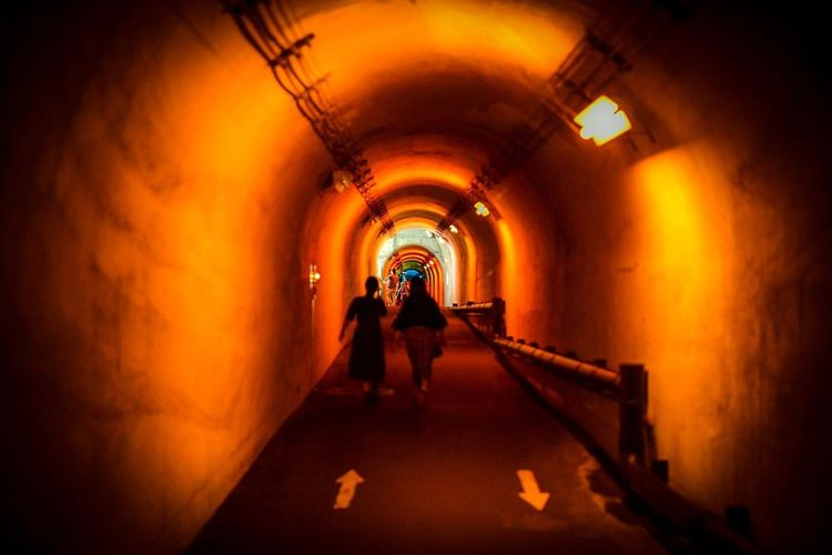 orange色のトンネル。 Architecture Real People Indoors  The Way Forward Walking Tunnel Direction Built Structure Lifestyles Orange Color Arch Illuminated Rear View Diminishing Perspective