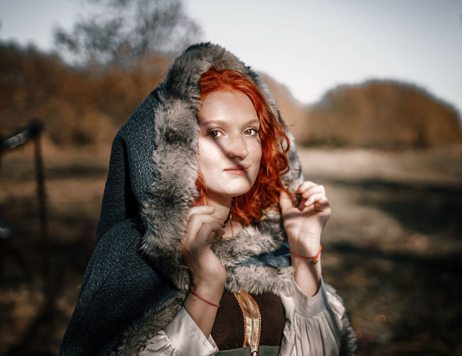 Portrait of young woman wearing fur coat standing outdoors