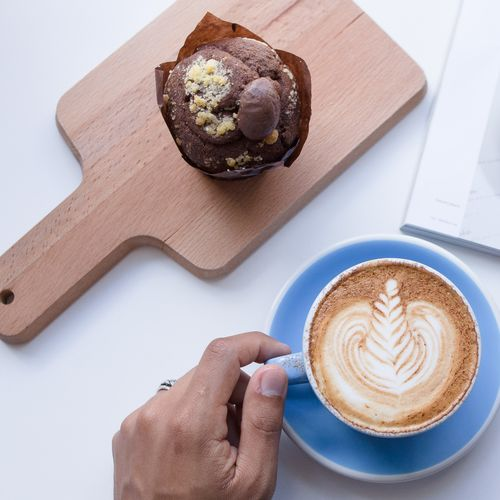 Blue Color Cappuccino Close-up Coffee - Drink Coffee Cup Day Drink Food Food And Drink Freshness Froth Art Frothy Drink High Angle View Holding Human Body Part Human Hand Indoors  Latte Morning Muffin One Person Real People Table White Background