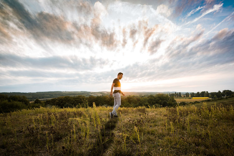 Sky One Person Cloud - Sky Land Leisure Activity Grass Lifestyles Scenics - Nature Plant Nature Standing Casual Clothing Field Beauty In Nature Landscape Non-urban Scene Tranquil Scene Outdoors Freedon Happy Shadows Shadow Sunset Sundown Boy