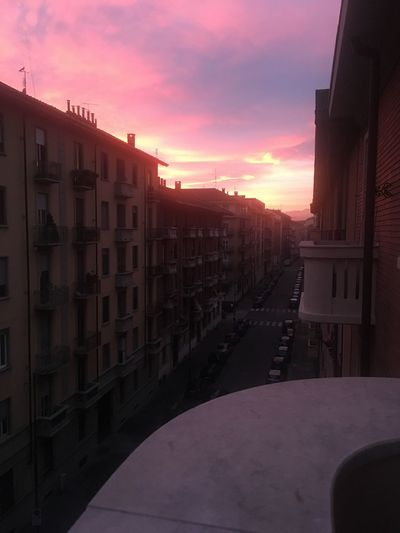 Street amidst buildings in town against sky during sunset
