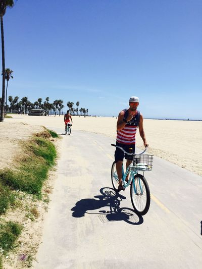Young men cycling along pathway at beach Bicycle Copy Space Riding Sunlight Two People Freedom Laguna Carefree African Ethnicity Caucasian Ethnicity Looking At Camera Vitality Enjoyment Lifestyles California Laughing Summer Fun Bike Happiness Coastal Landscapes With WhiteWall Moments Of Happiness