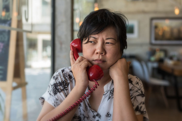 Serious woman talking on telephone at home
