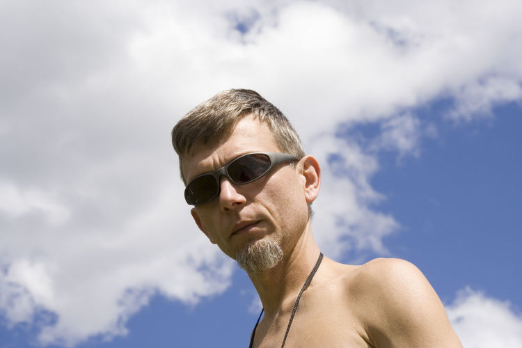 Low angle portrait of mature man against sky
