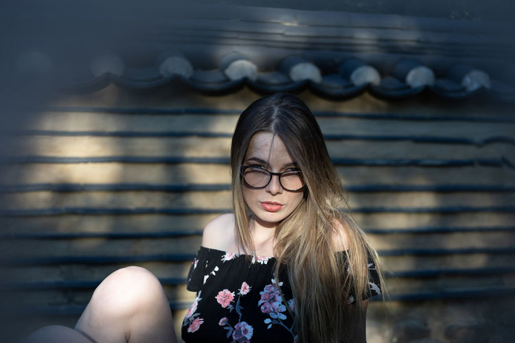 Portrait of beautiful young woman sitting by wall outdoors