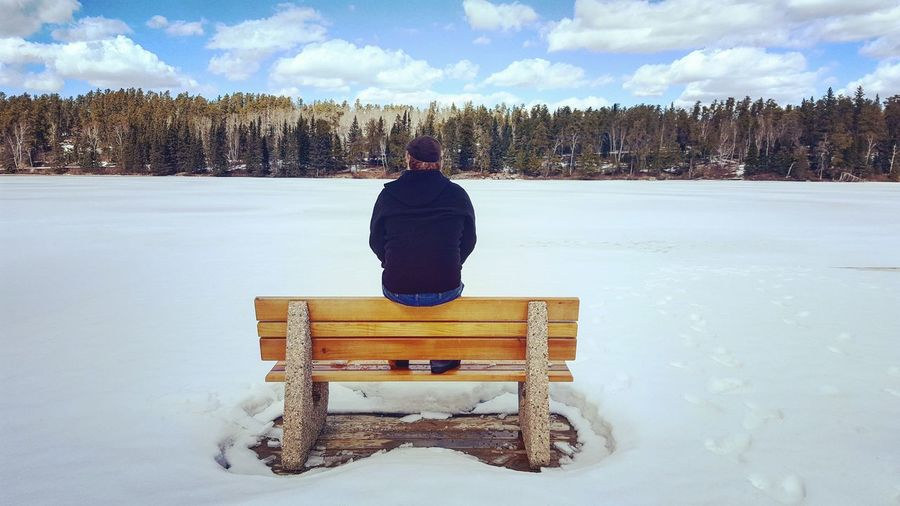 Rear view of man sitting on snow covered landscape