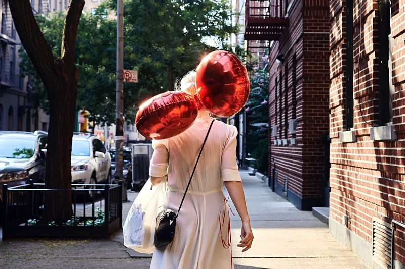 Woman with red balloons  standing in city