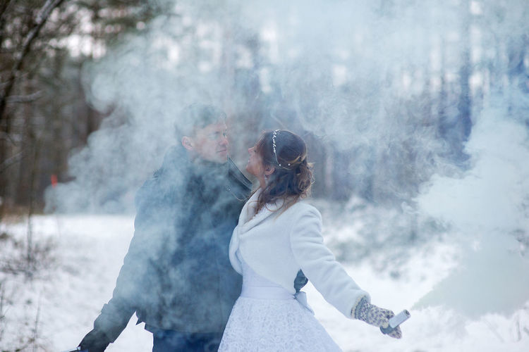 Close-up of couple with distress flare standing against tree during winter