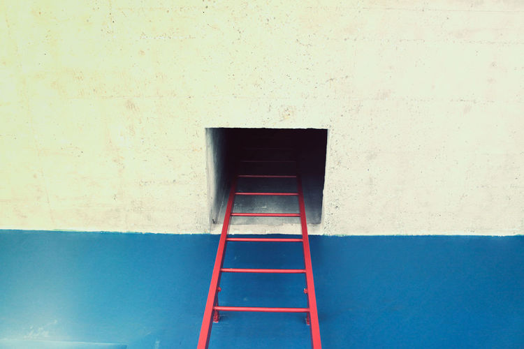 Low angle view of ladder on building wall
