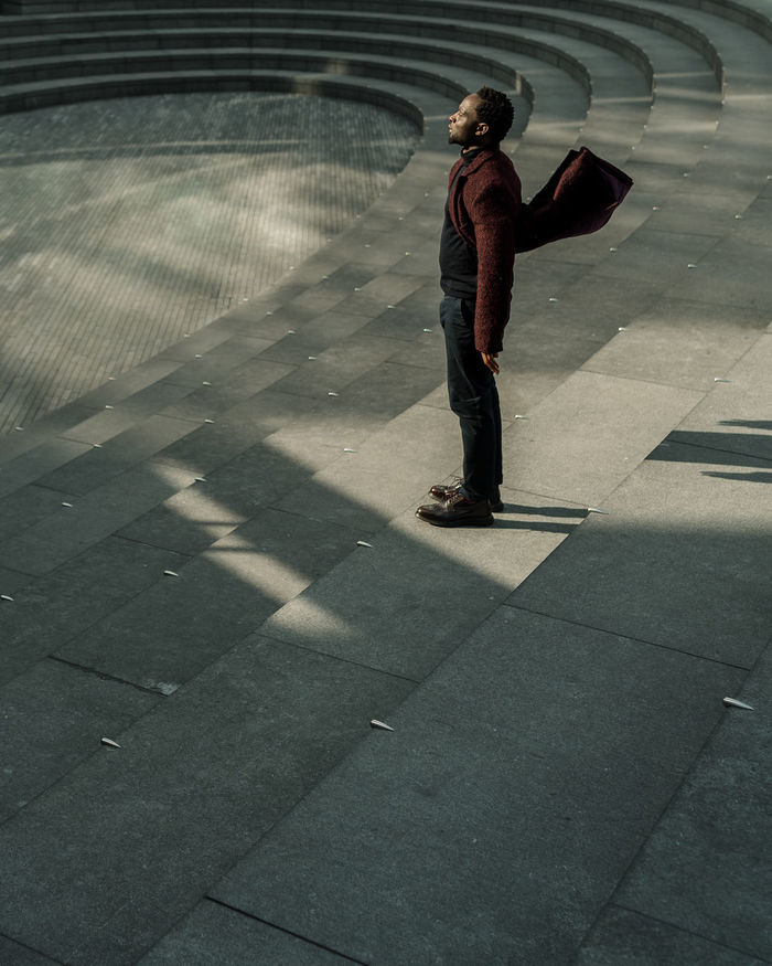 FULL LENGTH OF A MAN WALKING ON FOOTPATH