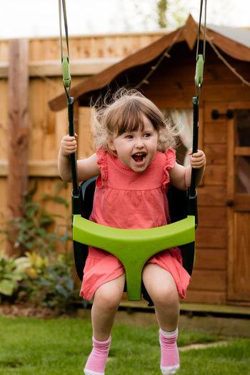 Happy girl screaming while swinging at backyard
