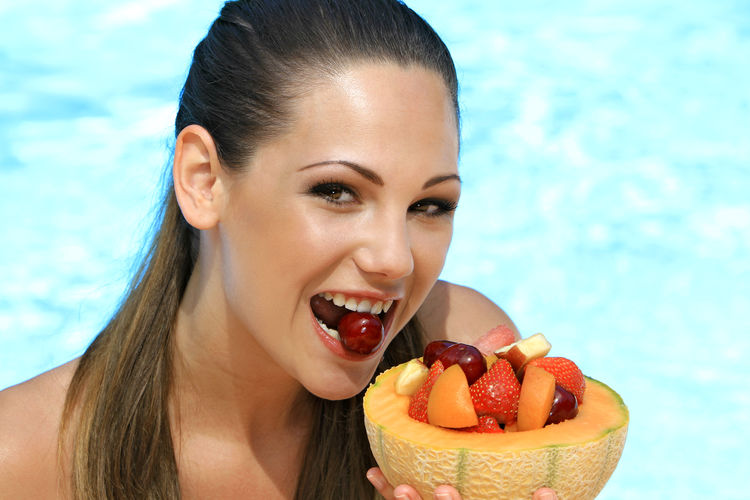 Portrait of beautiful smiling young woman eating fruits against swimming pool