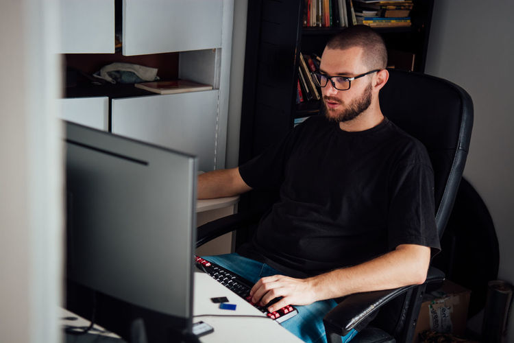 Side view of young man using computer while on chair at home