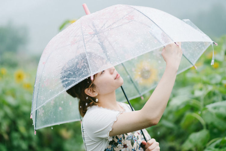 Young Woman Holding Transparent Umbrella On Rainy Day