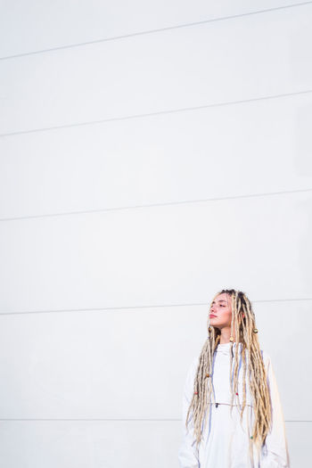 Futuristic fashionable young woman in white clothes One Person Long Hair Hair Standing Wall - Building Feature Women Blond Hair Hairstyle Front View Casual Clothing Copy Space Real People Lifestyles Portrait Day Leisure Activity Girls Young Adult Contemplation Teenager Beautiful Woman Innocence