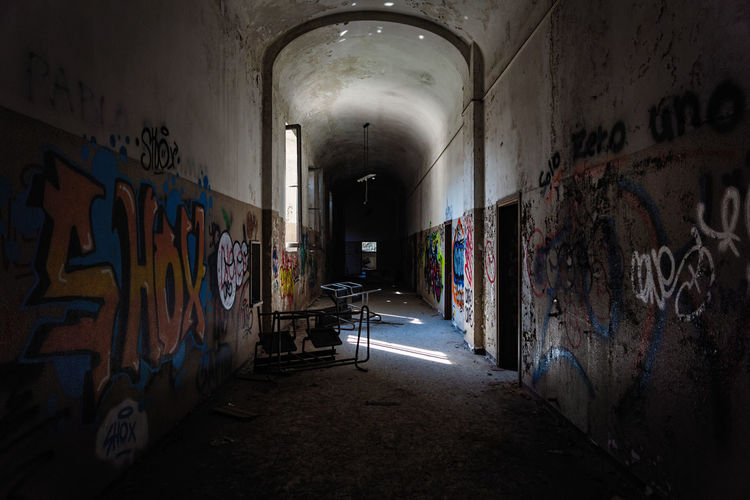 Mental Hospital  Graffiti Architecture Wall - Building Feature Abandoned Building Indoors  Creativity Built Structure Art And Craft Corridor Direction The Way Forward No People Arcade Old Tunnel Paint Messy Obsolete Deterioration Dirty Ruined Ceiling