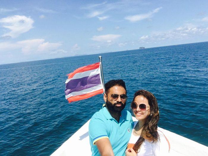 Couple sailing in sea against sky