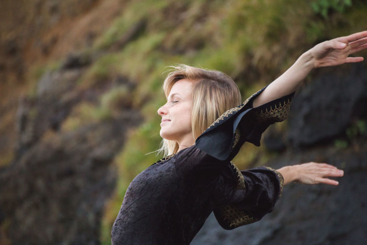 Side View Of Young Woman With Arms Outstretched Against Rocky Mountain