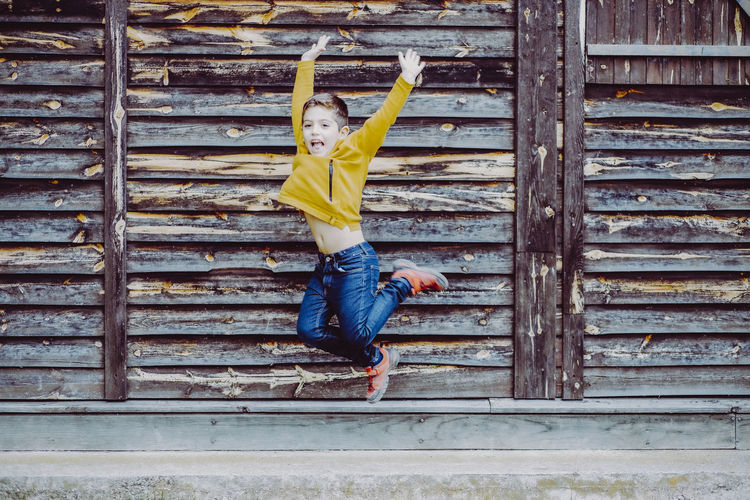 Full length of boy jumping against wooden wall
