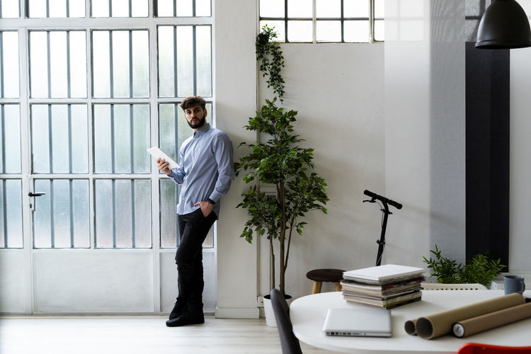 Side view of young man standing by window