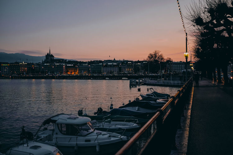 Scenic view of river by buildings against sky at sunset. genf, geneve, geneva, switzerland.