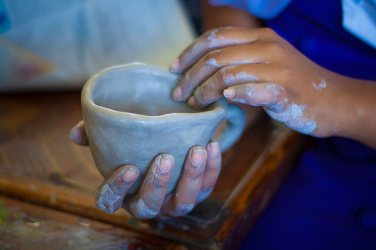 Cropped Image Of Person Making Cup With Clay