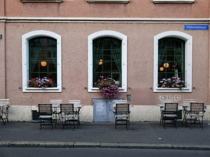 Flower pots on sidewalk against building