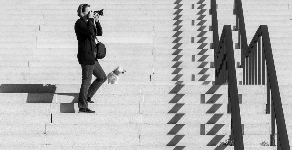 Side view of woman with dog photographing on staircase in city