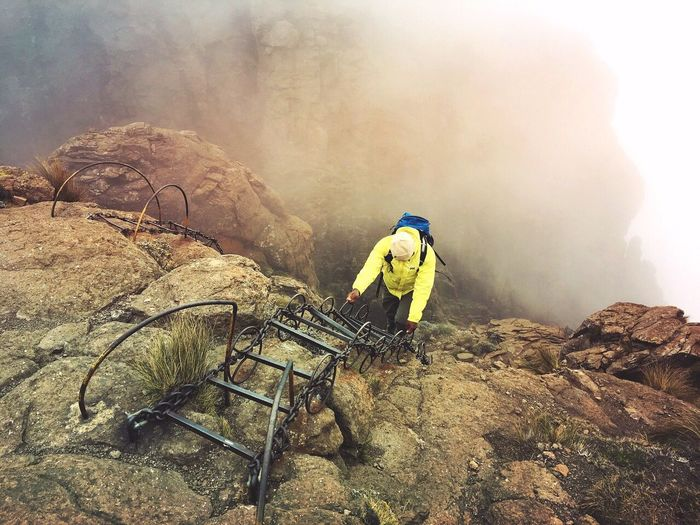 Man working on rock against sky