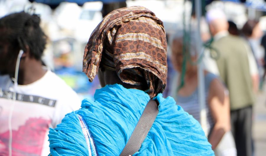 Rear view of woman covering head with scarf in city